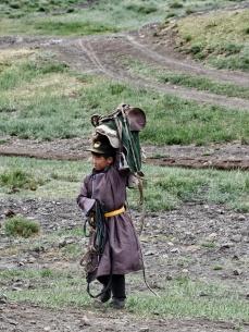 Kleiner Mongole beim Pferdesatteln vor der Geierschlucht, damit die Touristen die 3km rein reiten können